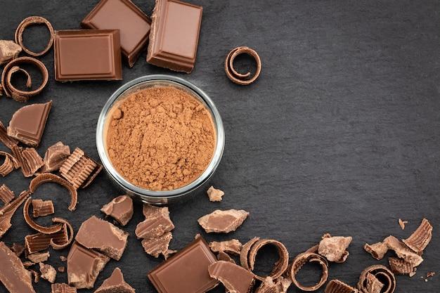 Pezzi di cioccolato rotti e polvere di cacao su uno sfondo scuro. vista dall'alto con copyspace per il tuo testo.