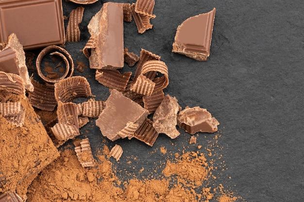 Pezzi di cioccolato rotti e polvere di cacao su uno sfondo scuro. vista dall'alto.