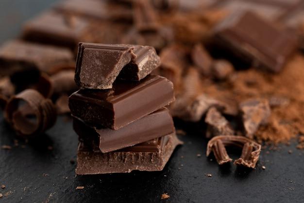 Pezzi di cioccolato rotti e polvere di cacao su uno sfondo scuro.