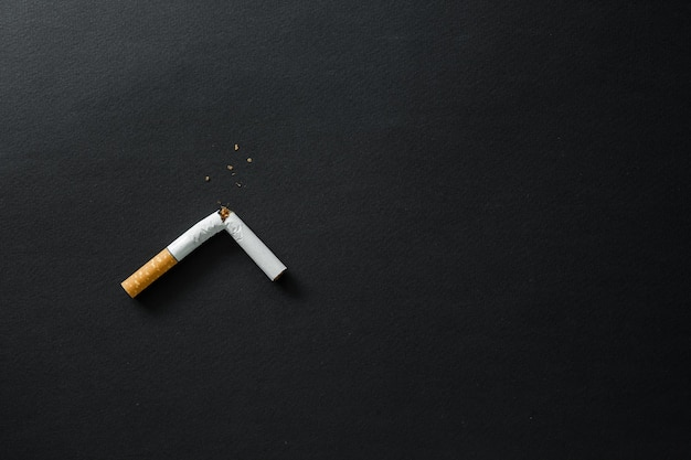 Sigaretta rotta su una superficie scura. smettere di fumare