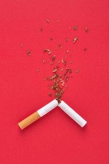Una sigaretta rotta e una spruzzata di tabacco per il concetto di smettere di fumare.