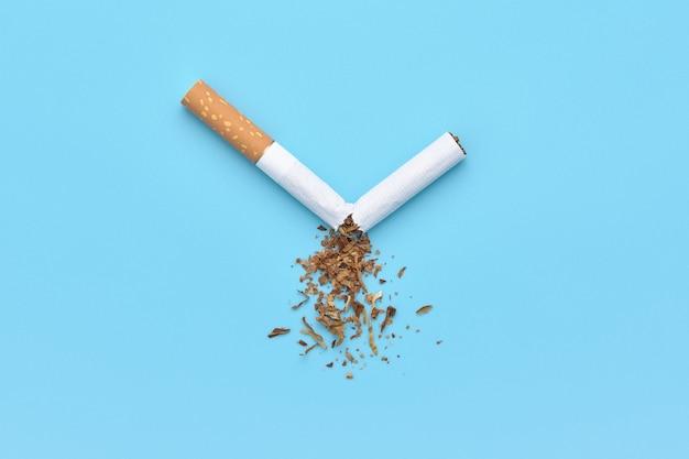 Una sigaretta rotta con tabacco sparso per il concetto di smettere di fumare.