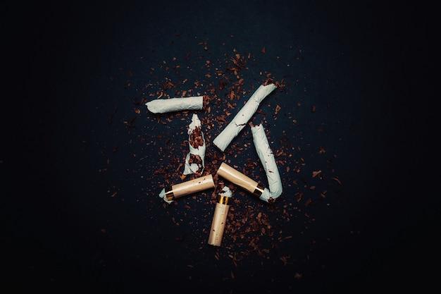 Sigaretta rotta con tabacco su uno sfondo nero isolato. la lotta contro la dipendenza da nicotina e la tossicodipendenza.