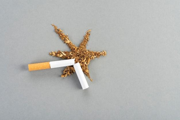 Una sigaretta rotta con il tabacco, il tabacco si diffonde sul tavolo grigio sotto forma di un'esplosione