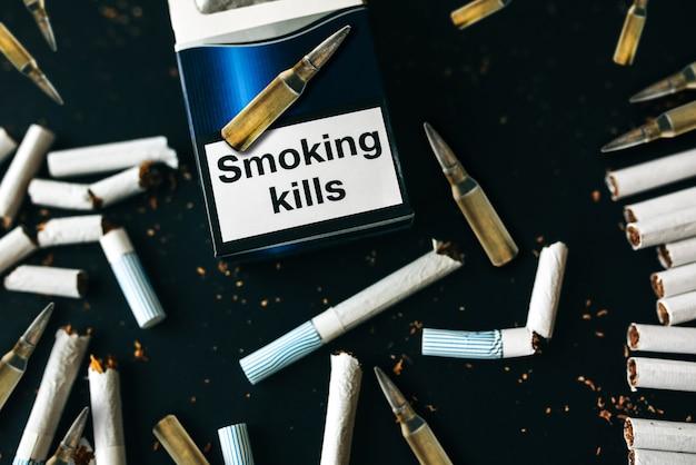 Sigarette rotte e proiettili. abitudine pericolosa. nocivo per la salute. fumare uccide.