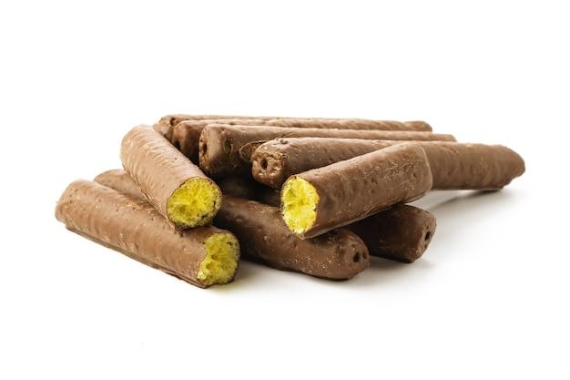 Bastoncini di mais rotti nel cioccolato in un primo piano al cioccolato su uno sfondo bianco isolato con ombre