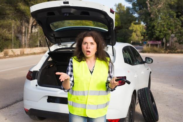 Auto in panne. donna in piedi accanto alla sua automobile ripartita sulla strada in attesa di emergenza
