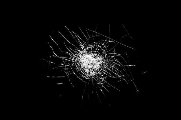 Il vetro rotto è isolato su uno sfondo nero. crepe bianche. foto di alta qualità