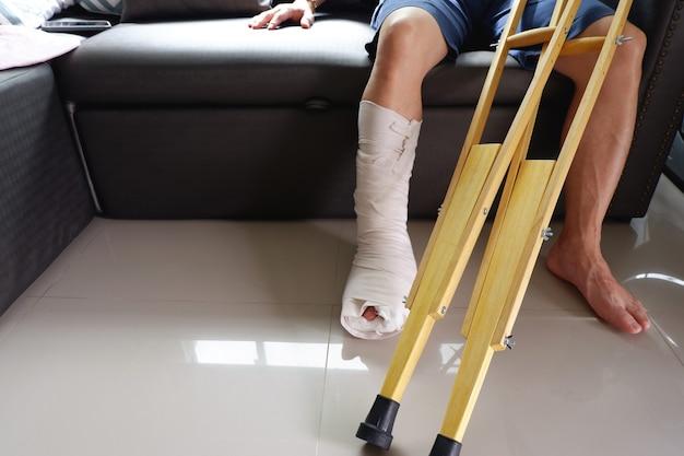 L'uomo con la gamba rotta e le stampelle di legno erano seduti sul divano di casa vista in sezione bassa e primo piano con spazio per le copie copy