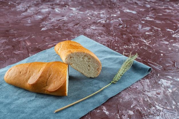 Pagnotta rotta di pane bianco con spiga di grano su una superficie leggera