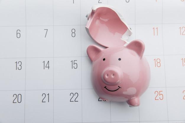 Salvadanaio rotto su uno sfondo di calendario bianco, risparmio e concetto di investimento. vista dall'alto.