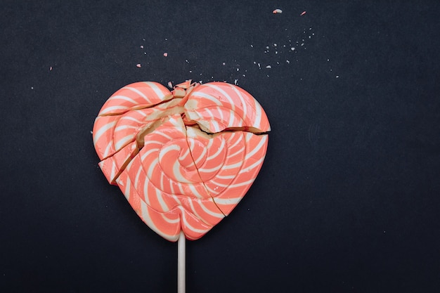 Cuore rosa spezzato. su uno sfondo nero. concetto di amore infruttuoso. ha rovinato il giorno di san valentino.