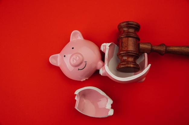 Porcellino salvadanaio rosa rotto con martelletto di legno del giudice su una legge rossa del fondo e sul concetto di fallimento