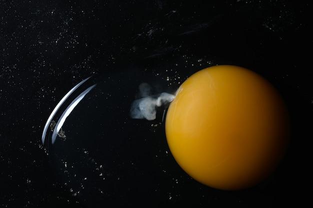 Rotto tuorlo d'uovo crudo su sfondo di pietra scura.
