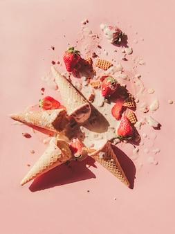 Gelato alla crema, alla fragola e al cioccolato rotto e rovesciato su superficie rosa. sopra la vista
