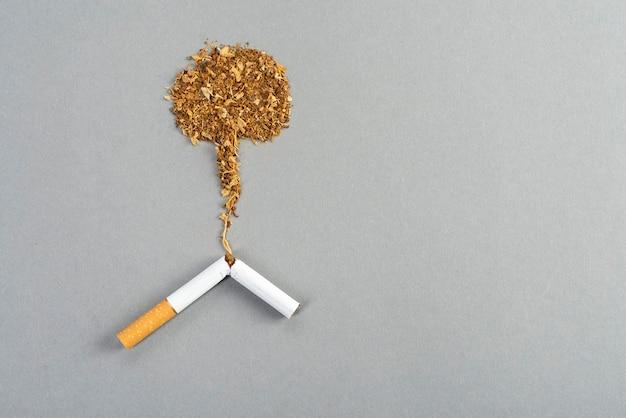 Sigaretta di tabacco rotta, tabacco che si spande sul tavolo grigio sotto forma di un'esplosione nucleare