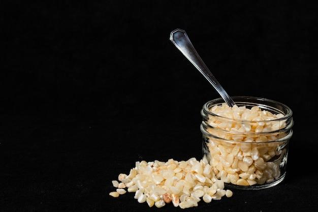 Semi di mais bianco rotti in un barattolo di vetro su una superficie nera. 45 gradi vista, spazio di testo.