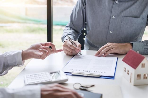 Agente di broker che presenta e consulta il cliente per firmare un contratto di assicurazione