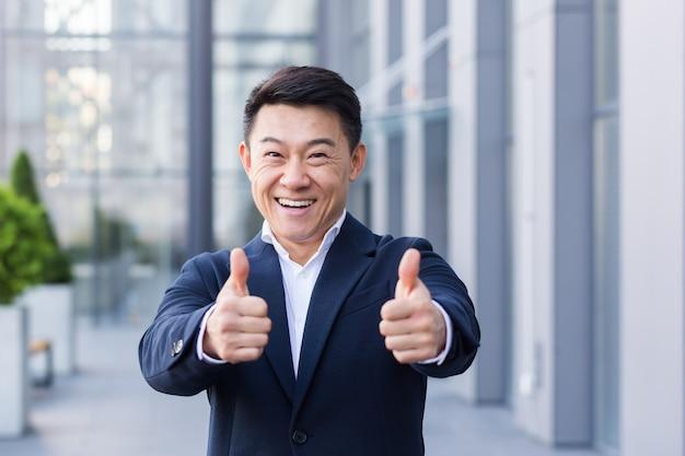 Broker uomo d'affari asiatico in tailleur felice guardando la fotocamera e mostrando i pollici in su