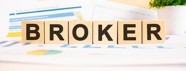 Parola di broker sui cubi di legno. lo sfondo è un grafico aziendale.