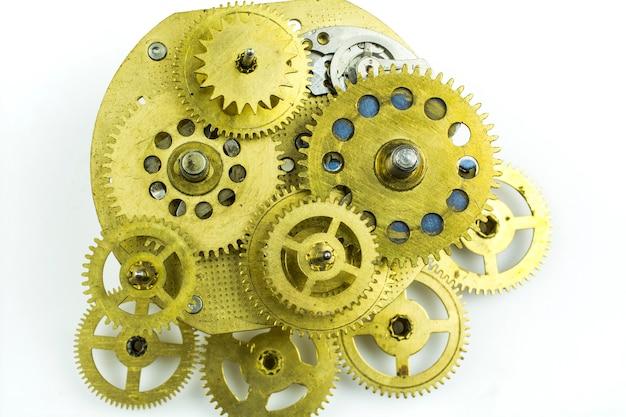 Ingranaggi in bronzo di un vecchio orologio rotto isolato su sfondo bianco di close-up.