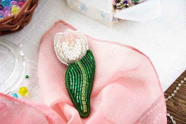Spilla fiore tulip fatto a mano con perline sul tavolo su sfondo rosa