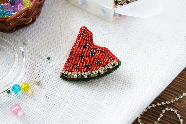 Spilla fatta a mano con perline multicolori sullo sfondo