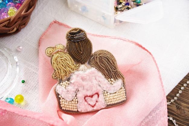 Spilla perline fatte a mano da mamma e figlia sul tavolo su sfondo rosa