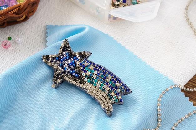 Spilla stella cometa fatta a mano con perline sul tavolo su sfondo blu