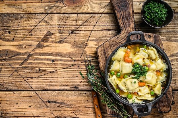 Zuppa di brodo con gnocchi di ravioli in padella. fondo in legno. vista dall'alto. copia spazio.