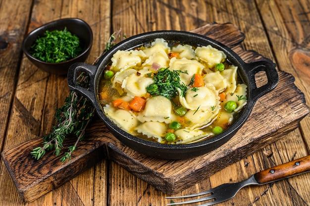 Zuppa di brodo con gnocchi di ravioli in padella. fondo in legno. vista dall'alto.