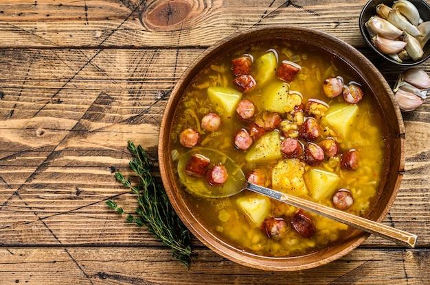 Brodo zuppa di piselli spezzati con salsicce affumicate in un piatto di legno. fondo in legno. vista dall'alto. copia spazio.