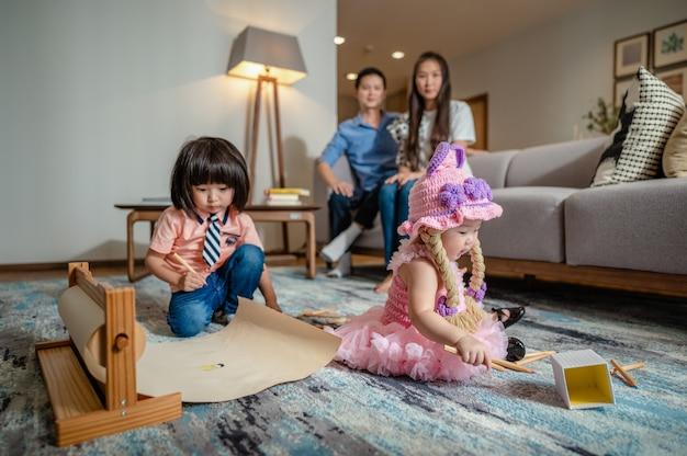Il fratello sta disegnando su carta con la sorellina sul tappeto nel soggiorno di casa genitori