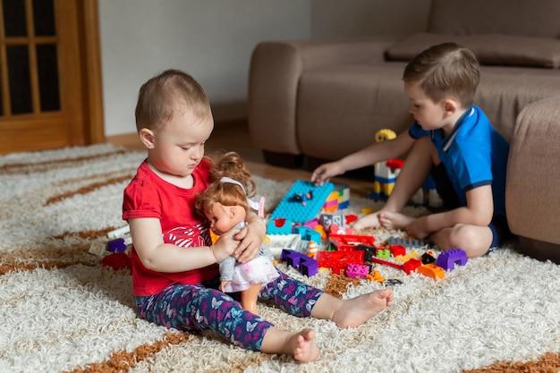 Il fratello sta giocando con un kit di costruzione sul tappeto e mia sorella sta giocando con una bambola.