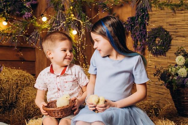 Fratello e sorella alla fattoria ridono e guardano le galline
