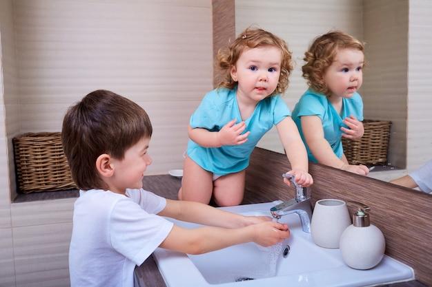 Fratello e sorella si divertono nella vasca da bagno igiene salute famiglia