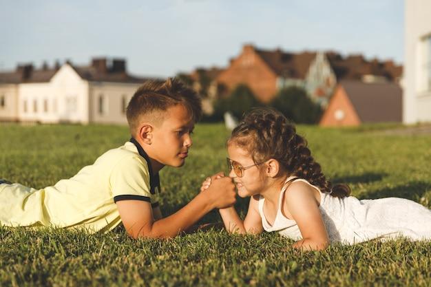 Fratello e sorella sdraiati sull'erba sono impegnati nel braccio di ferro.