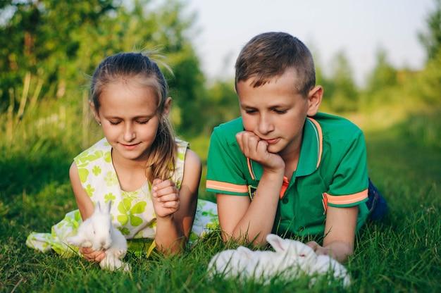 Fratello e sorella sdraiati sull'erba con coniglietti. coniglietto di pasqua