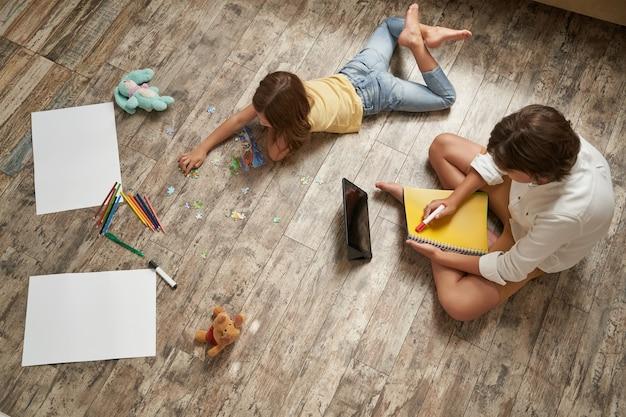 Fratello e sorella sdraiati sul pavimento di legno a casa e trascorrono del tempo insieme a una bambina che gioca