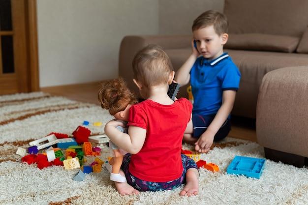Fratello e sorella giocano con un kit di costruzione e parlano su un telefono giocattolo.
