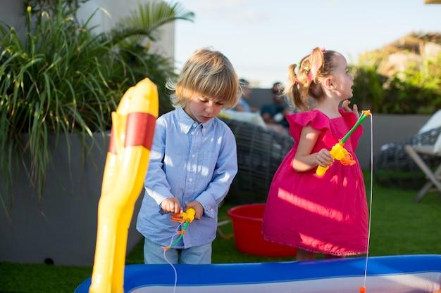 Fratello e sorella che giocano a pesca nella piscina per bambini