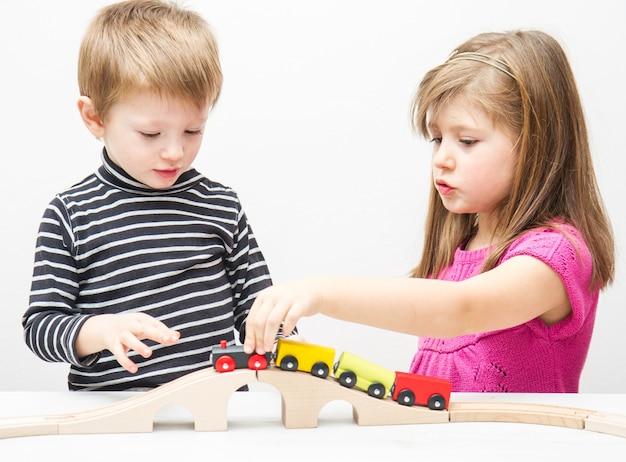 Fratello e sorella che giocano con il trenino di legno