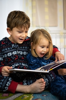 Fratello e sorella leggono un libro in pigiama a piedi nudi la sera dormono in famiglia