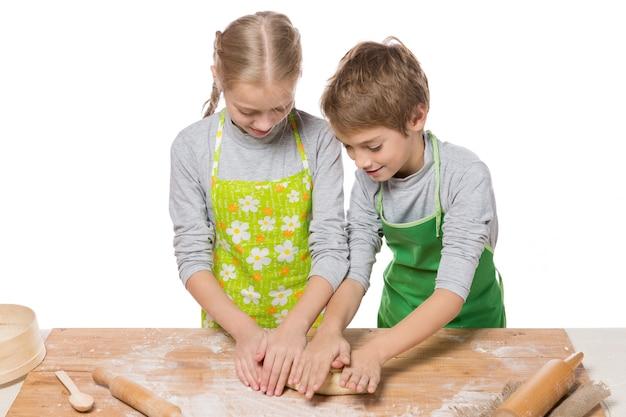 Fratello e sorella stendere la pasta per la cottura su un tavolo da cucina su sfondo bianco