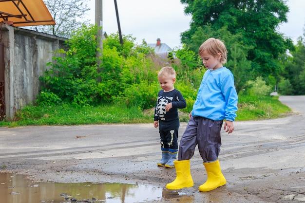 Fratello e sorella in stivali di gomma e impermeabile stanno giocando in una pozzanghera