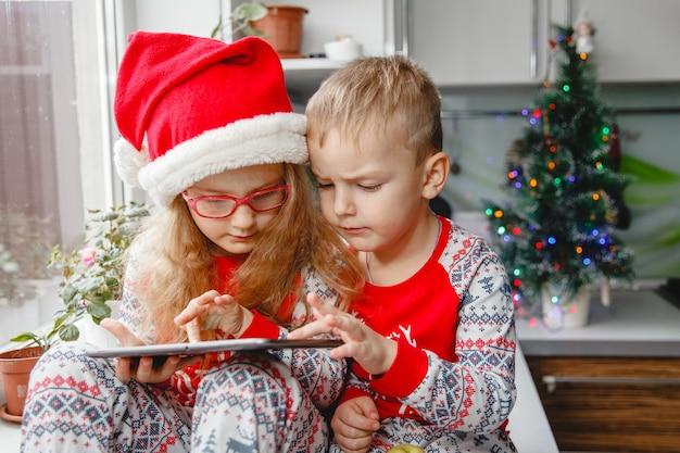 Fratello e sorella si siedono in cucina con i cappelli da babbo natale e guardano il blocco. i bambini scrivono una lettera a babbo natale
