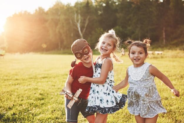 Fratello e due sorelle stanno giocando insieme. tre bambini che giocano con un aeroplano di legno all'aperto