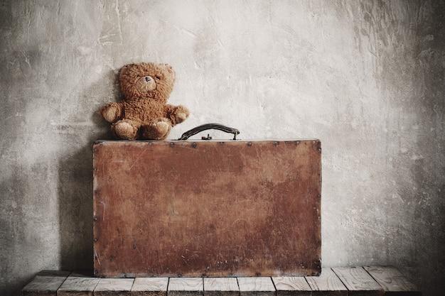 Brouwn orsacchiotto e vecchia valigia su sfondo grunge