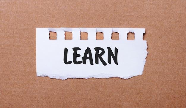 Su fondo marrone, carta bianca con la scritta learn