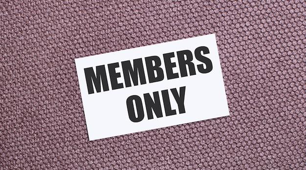 Su uno sfondo marrone, un cartoncino rettangolare bianco con il testo solo per i membri